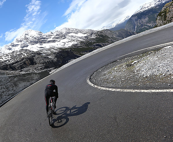 A cyclist climbing the road to Passo dello Stelvio with snowy mountains in the background