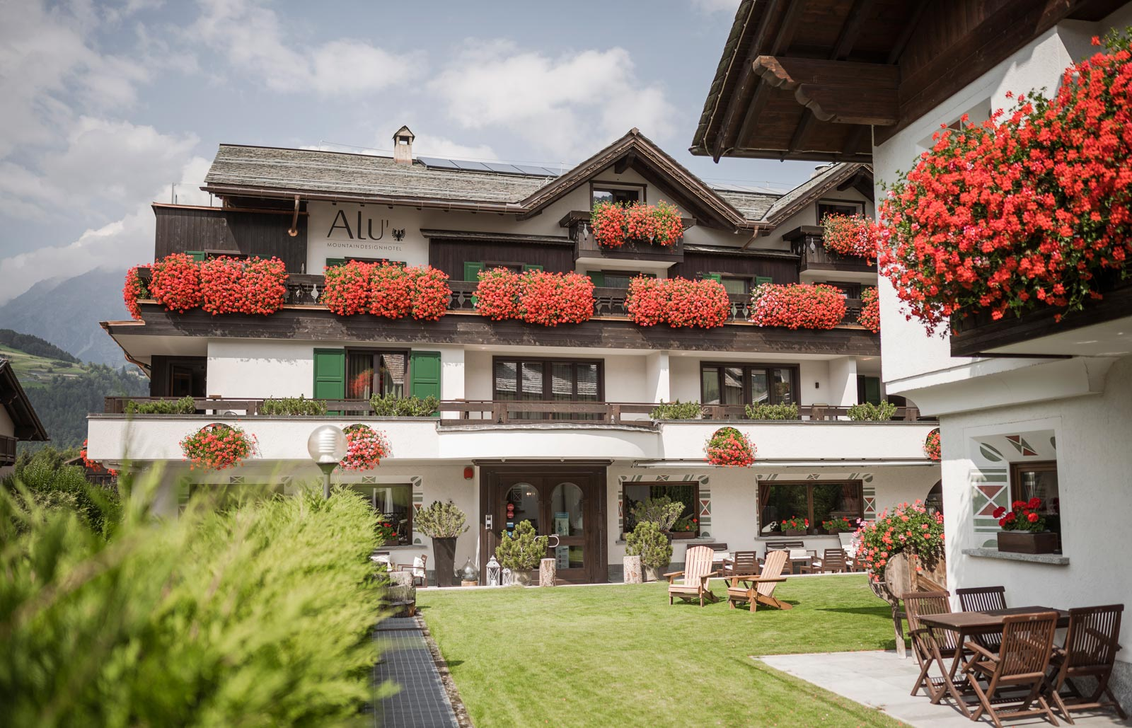 Sitting room corner with leather armchairs and chandelier at Hotel Alù a Bormio