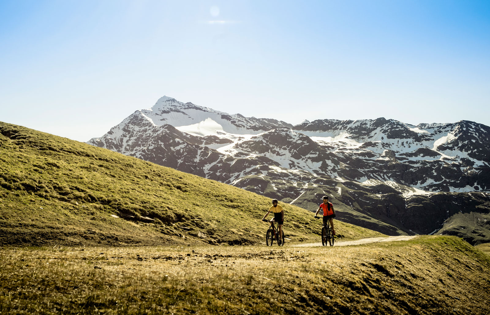 Cyclists on a mountain path with snowy peaks in the background