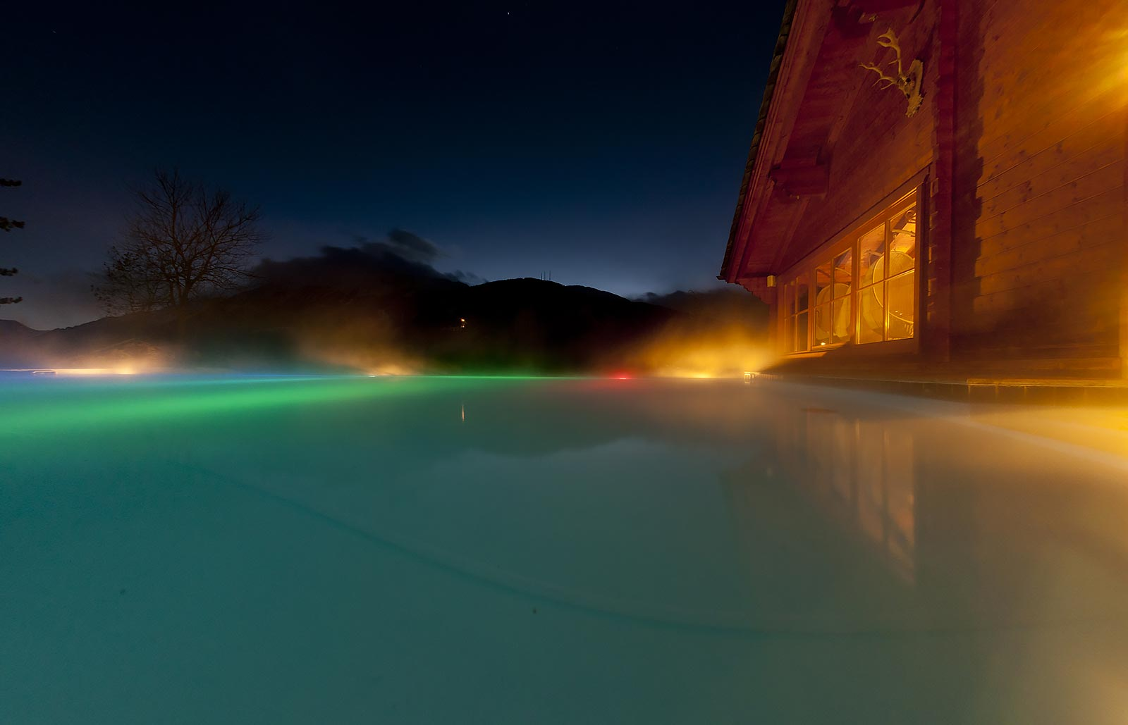 Hot water tub with lights on the outside of a wooden alpine house