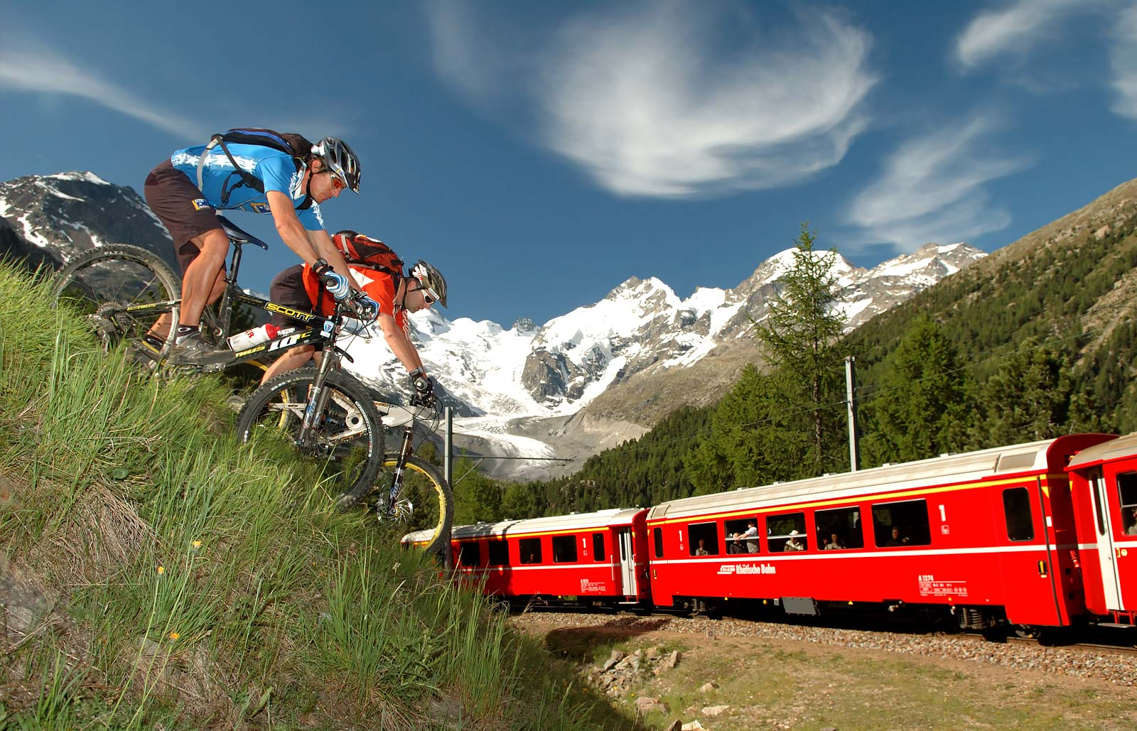 Two cyclists on a hill watching the Bernina train pass